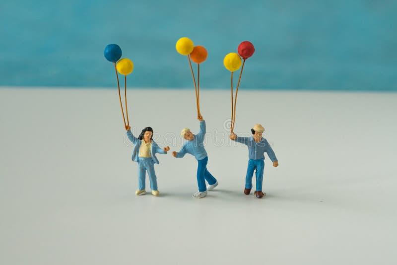 Miniaturleute mit der Familie, die Ballon mit blauem Farbbac hält lizenzfreie stockfotos