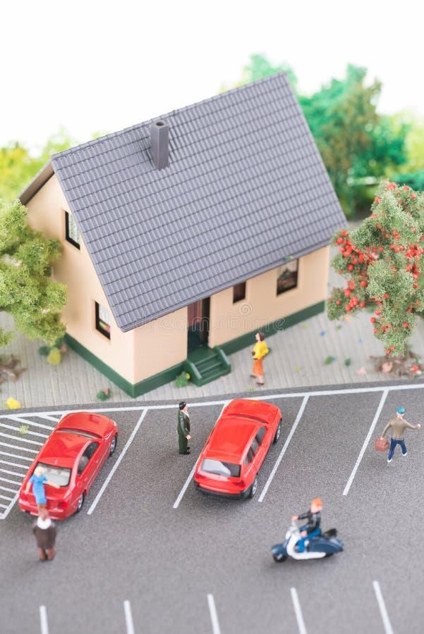 Miniaturleute, Reihenhaus und eine verkehrsreiche Straße modellieren stockfotografie