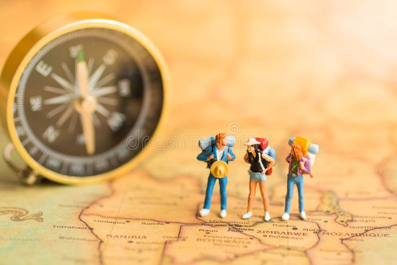 Miniaturleute: Reisende stehen auf der Kartenwelt und gehen zum Bestimmungsort Gebrauch als Dienstreisekonzept stockbild
