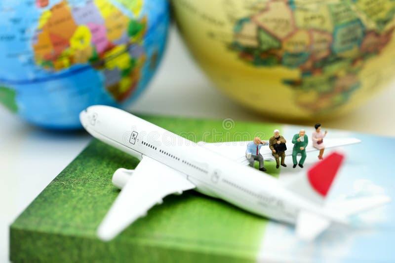 Miniaturleute: Sitzen auf Flugzeugflügel für Reise um Th lizenzfreie stockfotos