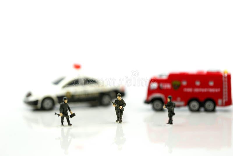 Miniaturleute: Soldatteam mit Löschfahrzeug und Polizeiwagen lizenzfreie stockfotografie