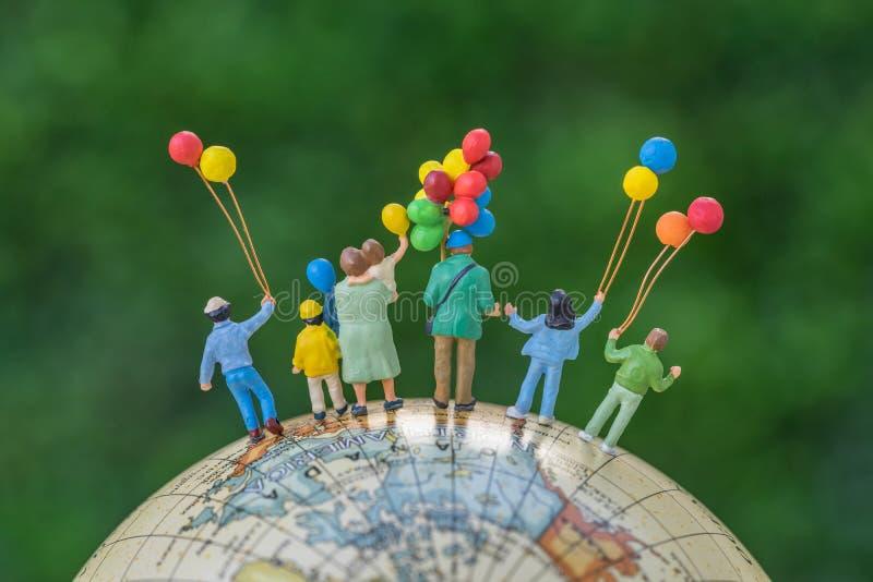 Miniaturleute stellen die hintere Ansicht der glücklichen Familie balloo halten dar stockbilder