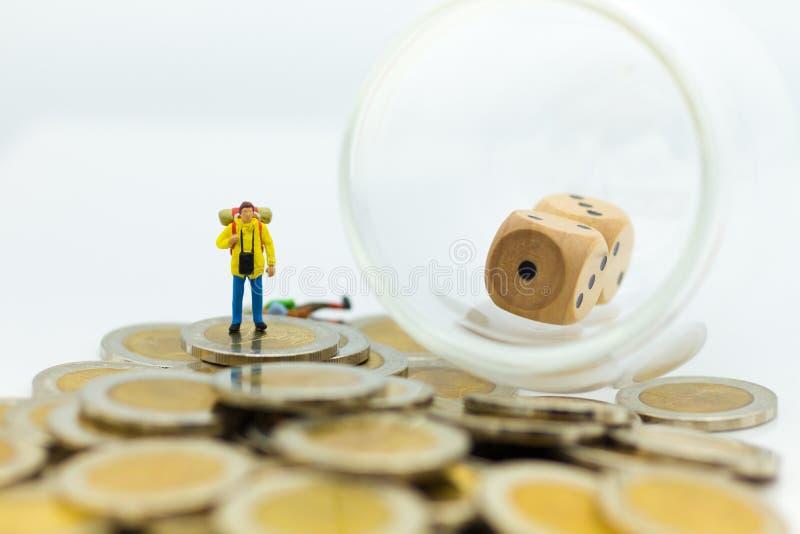 Miniaturleute: Touristen stehen auf der Münze mit Würfeln innerhalb des Glases Bildgebrauch für Reise- und Risikokonzept stockbilder