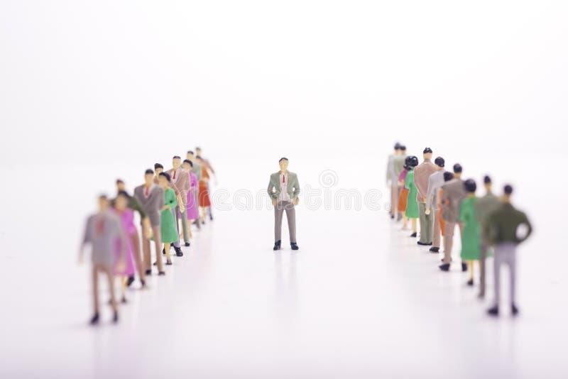 Miniaturleute in zwei Linien herüber miteinander mit Chef herein lizenzfreie stockfotografie