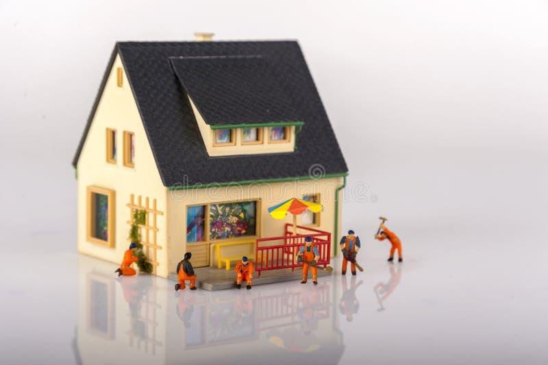 Miniaturleutearbeitskräfte und -haus stockfotos