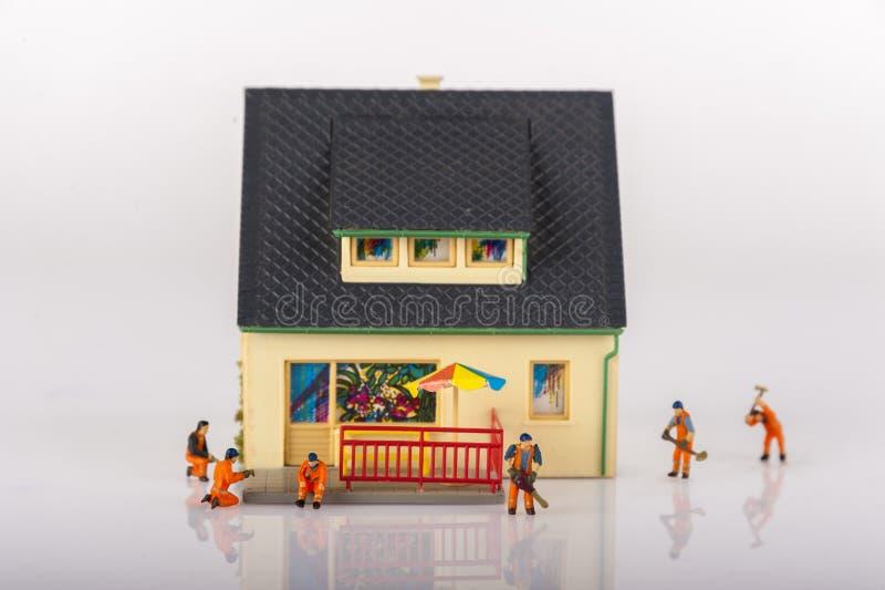 Miniaturleutearbeitskräfte und -haus stockfoto