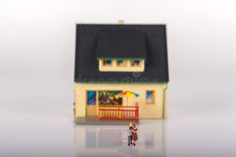 Miniaturleutefamilie und -haus lizenzfreie stockfotografie