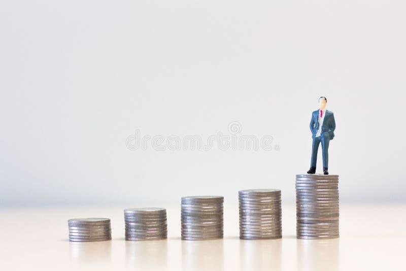 Miniaturleutegeschäftsmänner, die auf Stapel Münzen stehen stockbilder