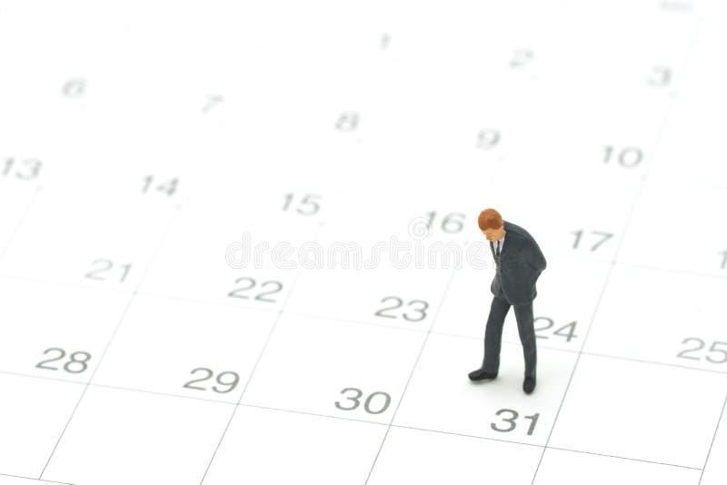 Miniaturleutegeschäftsmänner, die auf weißem Kalender unter Verwendung als Hintergrundgeschäftskonzept und Finanzkonzept stehen lizenzfreie stockfotografie