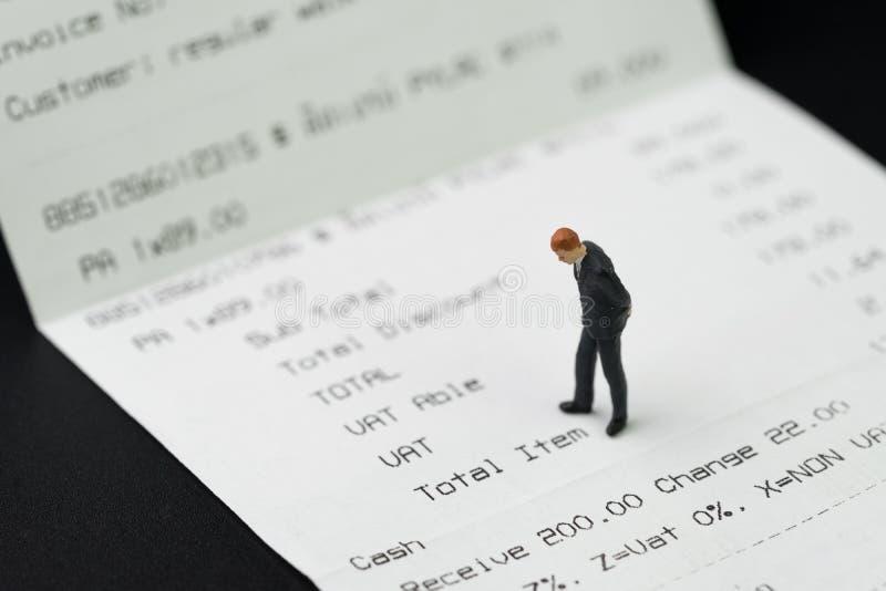 Miniaturowa biznesmen figurki pozycja na drukowanym płatniczym invoi obrazy stock