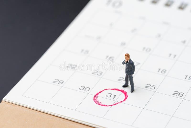 Miniaturowa biznesowego m??czyzny pozycja na desktop kalendarzu z czerwonym okr?giem na ostatnim dniu, 31 rezygnacji znacz?co dat obraz royalty free