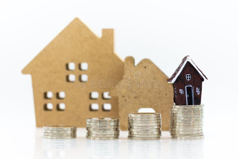 Miniaturowa budowa: Dom odpoczywa z stertą monety Wizerunku use hipoteka i nieruchomości inwestycja fotografia stock