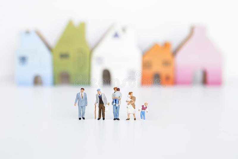 Miniaturowa grupa różni ludzie nad zamazanym domem jakby fotografia royalty free