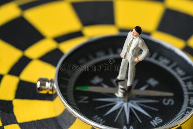Miniaturowa postać biznesowego mężczyzna pozycja na kompasie w centrum zdjęcia stock