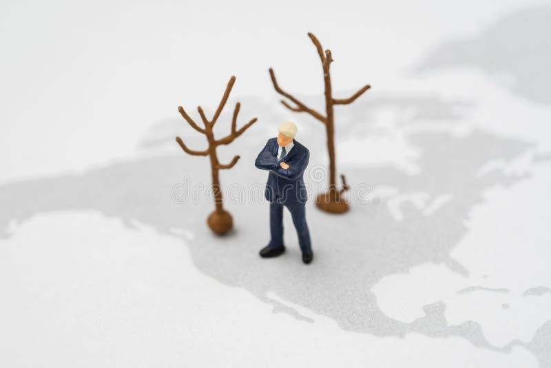 Miniaturowa USA Ameryka prezydenta lidera pozycja na usa mapie z wysuszonymi drzewami reprezentuje zmiana klimatu lub globalnego  zdjęcie stock