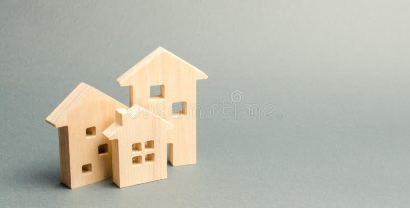 Miniaturowi drewniani domy na szarym tle mieszka? nieruchomo?ci dom?w prawdziwego czynszu sprzeda?y D?ugookresowi do wynaj?cia mi fotografia royalty free