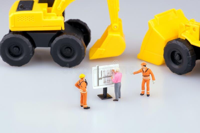 Miniaturowi inżynierii ludzie, architektura pracuje na budowa rysunku i fotografia stock