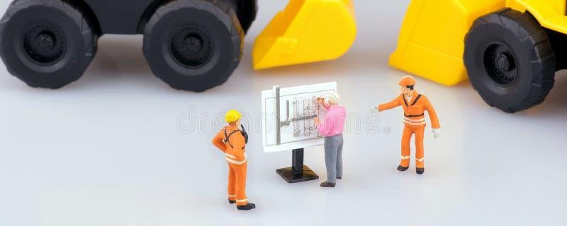 Miniaturowi inżynierii ludzie, architektura pracuje na budowa rysunku i obrazy royalty free