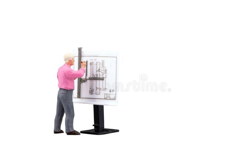 Miniaturowi inżynierii ludzie pracuje na budowa rysunku odizolowywającym z ścinek ścieżką zdjęcia stock