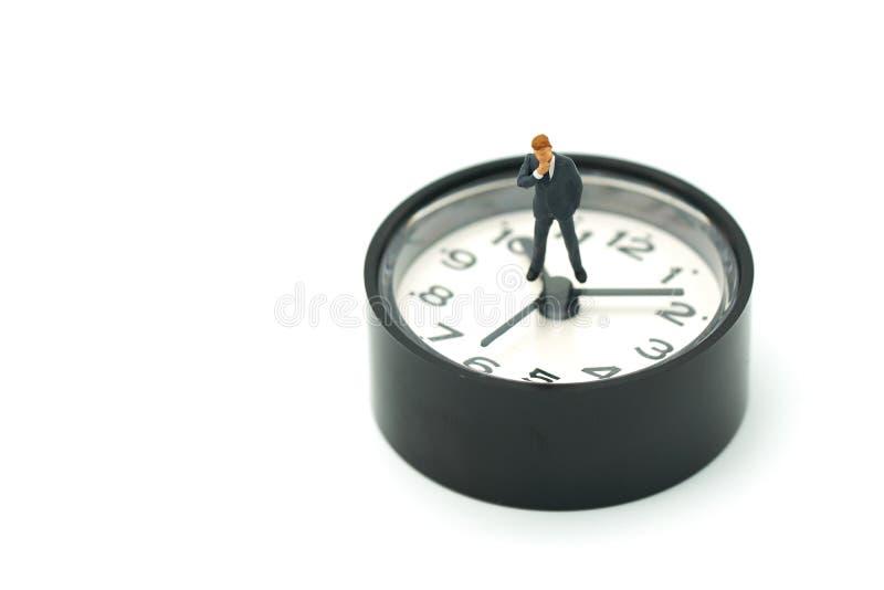 Miniaturowi ludzie biznesmenów analizują pozycję na zegarze jako tło strategii pojęcie i biznesu pojęcie zdjęcie royalty free
