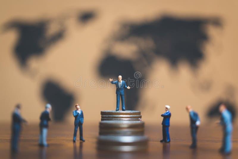 Miniaturowi ludzie: Biznesmen na stercie moneta, pieniądze i financ, zdjęcia stock