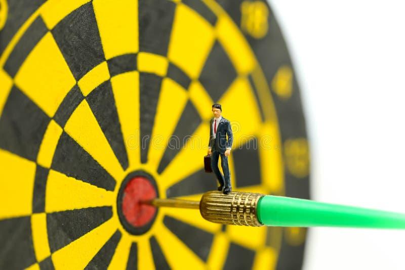 Miniaturowi ludzie: biznesmen na strzałki strzałkowatym ciupnięciu w celu centrum dartboard celu biznes i zwycięstwa pojęcie, dok zdjęcie stock