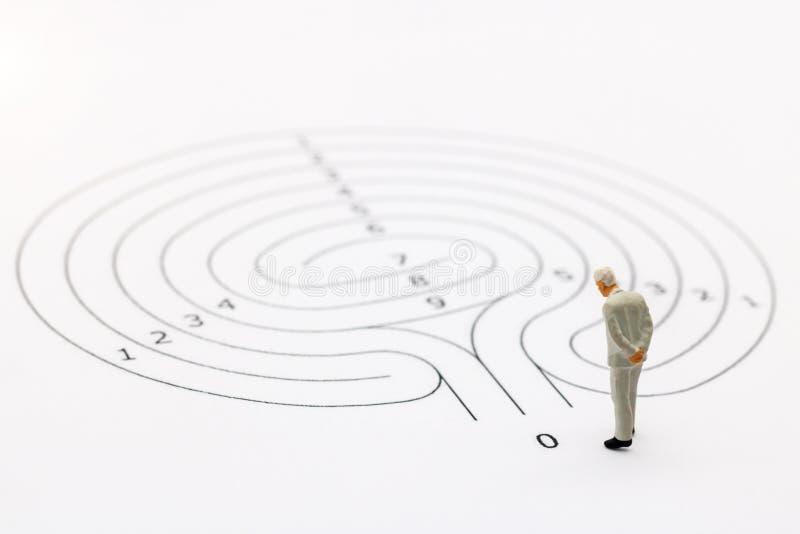 Miniaturowi ludzie: Biznesmen pozycja na początku punkcie labirynt fotografia royalty free