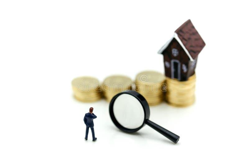 Miniaturowi ludzie: biznesmen pozycja z stertą monety mone zdjęcia stock