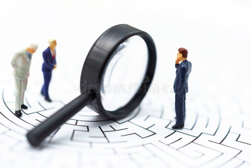 Miniaturowi ludzie: Biznesmen używa powiększać - szkło znajdować trasę na labiryncie Pojęcia znajdować rozwiązanie, rozwiązywanie obrazy stock
