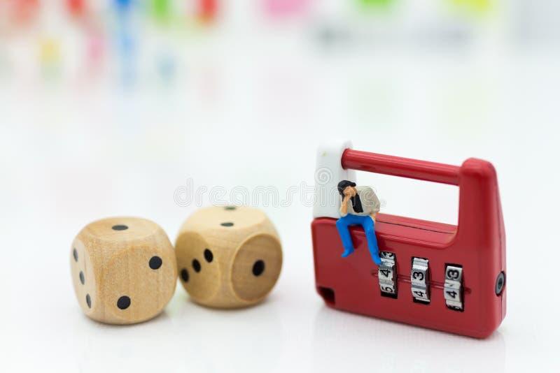 Miniaturowi ludzie: biznesmena obsiadanie na ochron kostka do gry i kluczu Wizerunku use dla tło systemu bezpieczeństwa, kilof, b zdjęcia stock