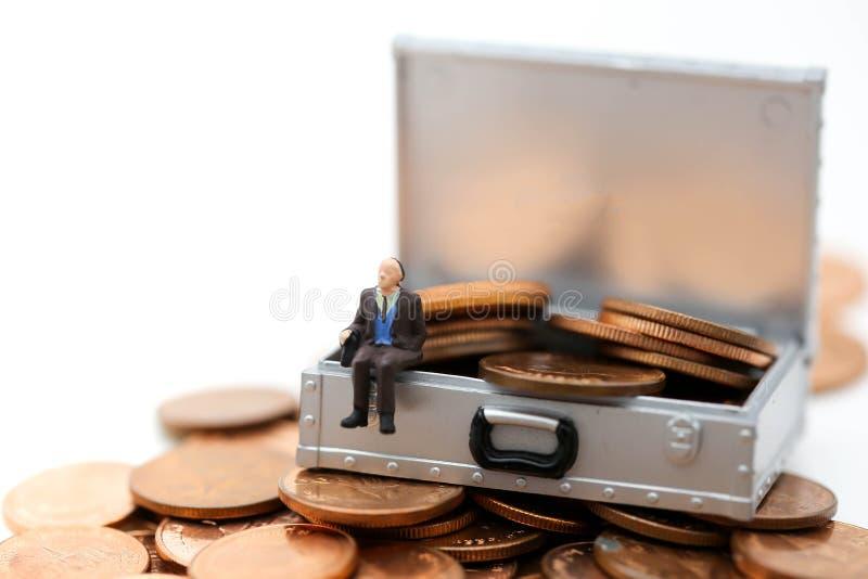Miniaturowi ludzie: biznesmena obsiadanie na pieniądze lub monetach w Ches zdjęcie stock