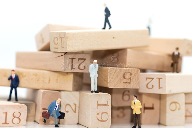 Miniaturowi ludzie: Biznesmeni stoi w różnorodnych pozycjach drewniane liczby, wskazuje sekwencję praca zdjęcia stock