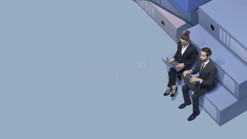 Miniaturowi ludzie biznesu siedzi i pracuje zdjęcie royalty free