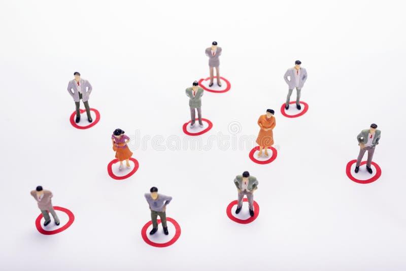 Miniaturowi ludzie biznesu w conection spiskują nad białym backdro zdjęcia stock