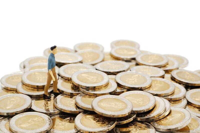 Miniaturowi ludzie chodzi na stosie nowe 10 Tajlandzkiego bahtu monet obraz royalty free