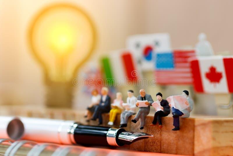 Miniaturowi ludzie czyta i siedzi na drewnie z lampowym pomysłem używać jako tło, edukacja lub biznesu pojęcie, obrazy royalty free