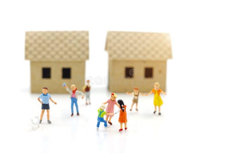 Miniaturowi ludzie dzieci bawić się z domami, szczęśliwy rodzinny dzień zdjęcie stock
