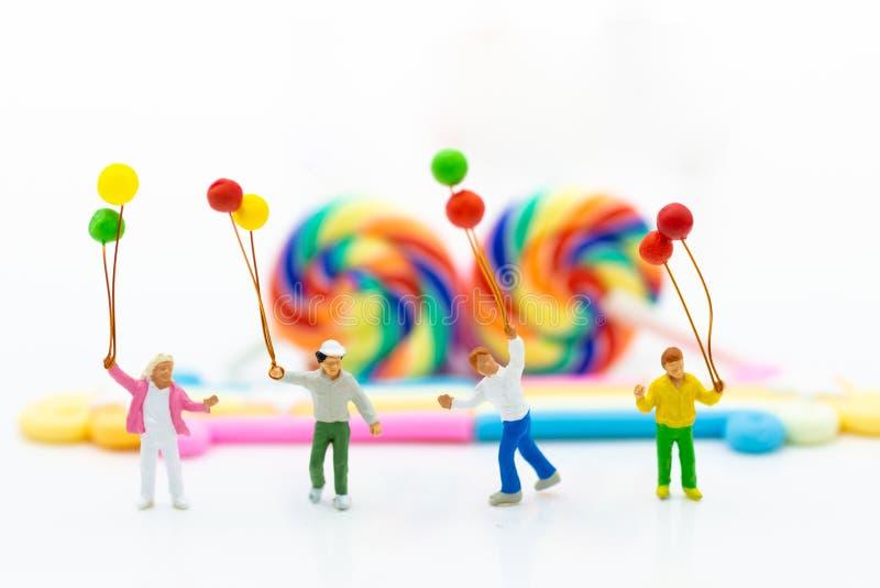 Miniaturowi ludzie: Dzieci trzyma balonowymi z kolorowym cukierki i lizaki r zdjęcia royalty free