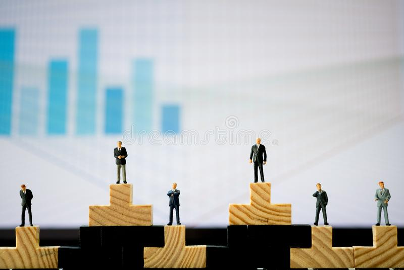 Miniaturowi ludzie: Each biznesmeni stoj? na drewnianym bloku w r??nej pozycji zdjęcie royalty free