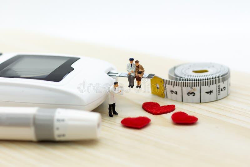 Miniaturowi ludzie: Glikoza metr z lancetem Wizerunku use dla medycyny, cukrzyce, opieki zdrowotnej pojęcie zdjęcia stock