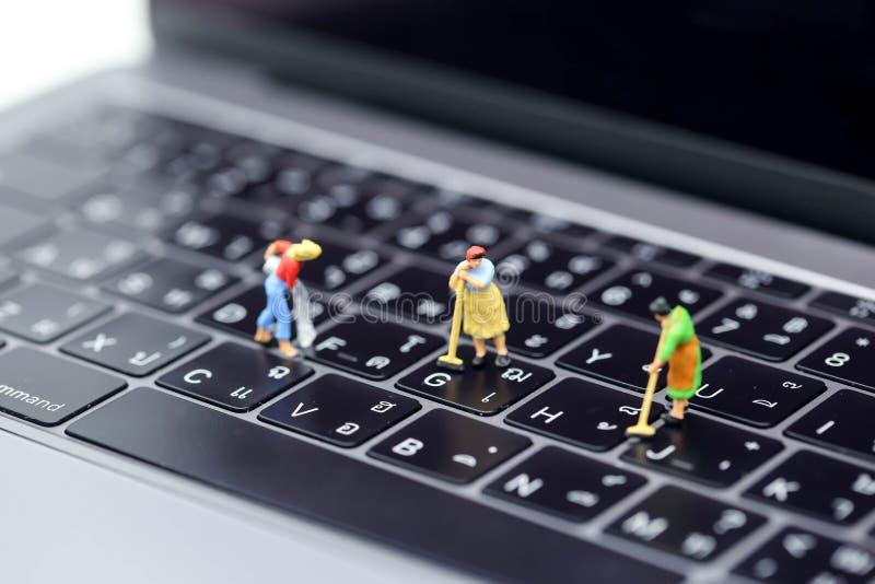 Miniaturowi ludzie: Gosposia lub gospodyni domowa czyści laptop zdjęcia royalty free