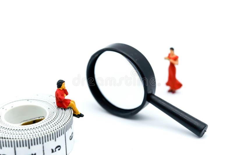 Miniaturowi ludzie: gruby kobiety obsiadanie na taśmy spojrzenia sli miarze obraz stock