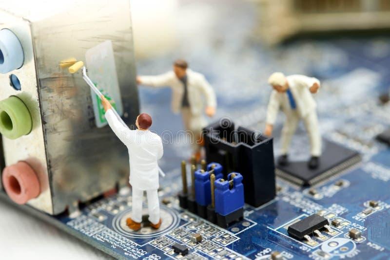 Miniaturowi ludzie: inżynier i pracownik pracuje na komputerowym mainb zdjęcia stock