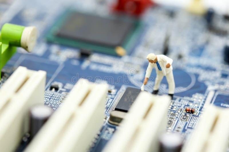 Miniaturowi ludzie: inżynier i pracownik pracuje na komputerowym mainb obrazy stock