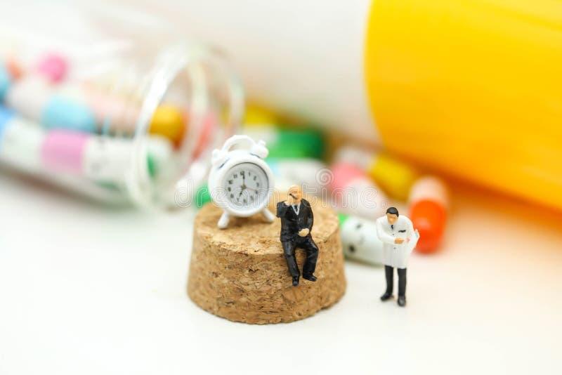 Miniaturowi ludzie: Lekarka i pacjent z kapsuła ałunami i pigułką obrazy stock