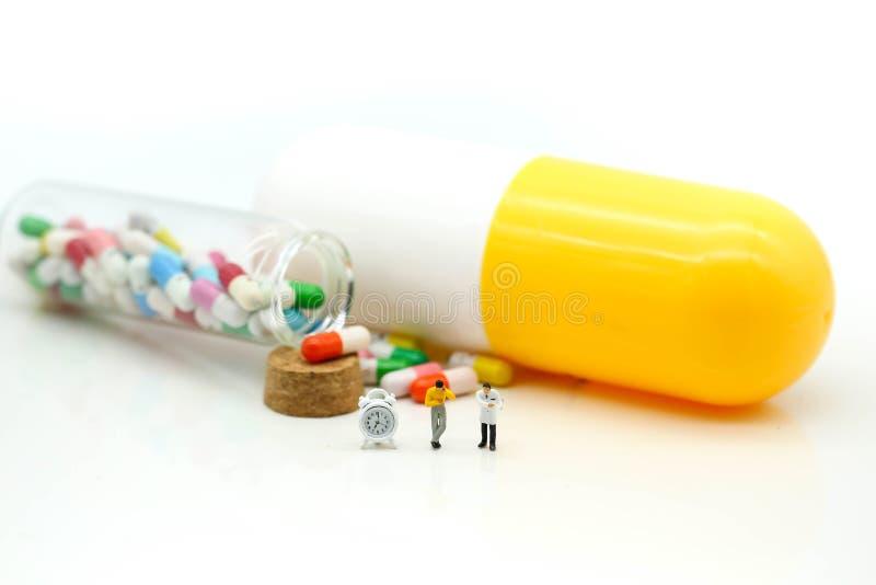 Miniaturowi ludzie: Lekarka i pacjent z kapsuła ałunami i pigułką fotografia stock