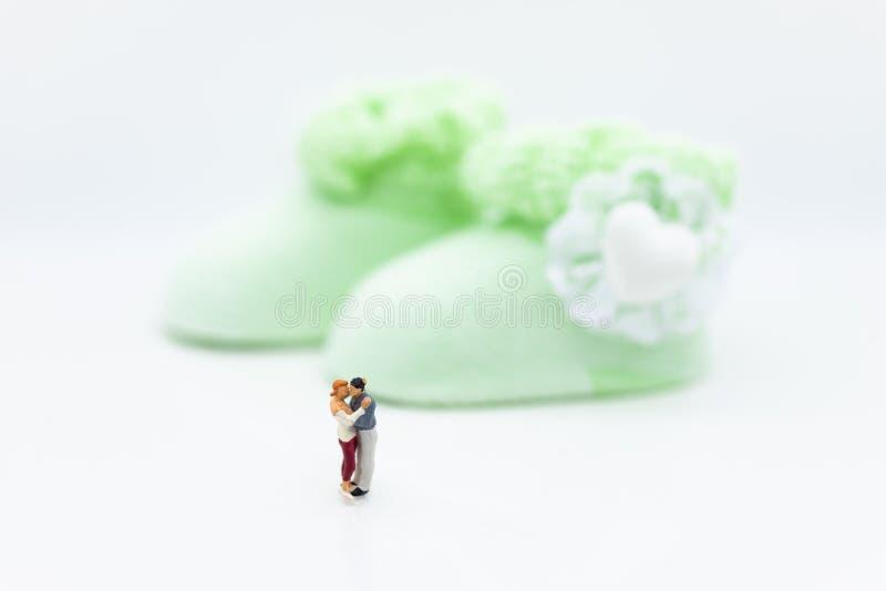 Miniaturowi ludzie: Mężczyzna i kobieta ściskamy wpólnie, czekać na dziecka w przyszłości Wizerunek używa dla robi nowej rodziny zdjęcie royalty free