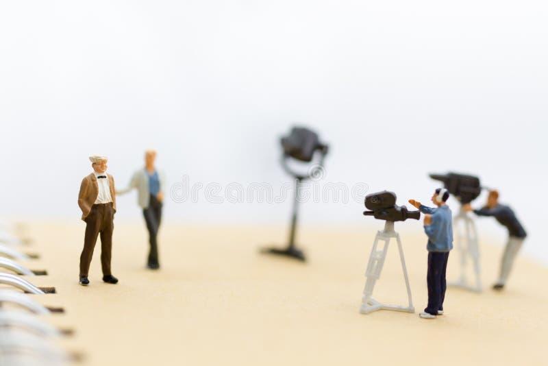 Miniaturowi ludzie: Mała drużyna tv reporter z osobistość wywiadami, produkci telewizi pojęcie obraz royalty free