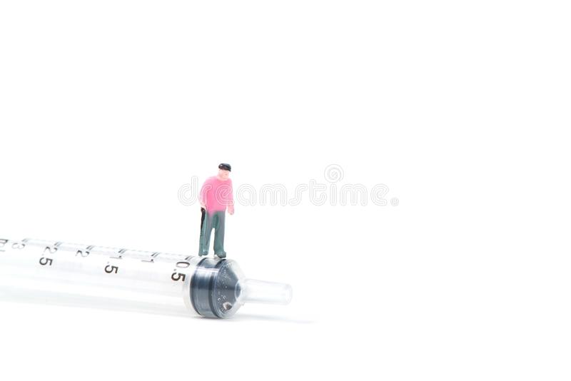 Miniaturowi ludzie, mały postać stary człowiek lub pacjent z dużą strzykawką, odizolowywającą na białym tle, zdrowy pojęcie zdjęcia royalty free