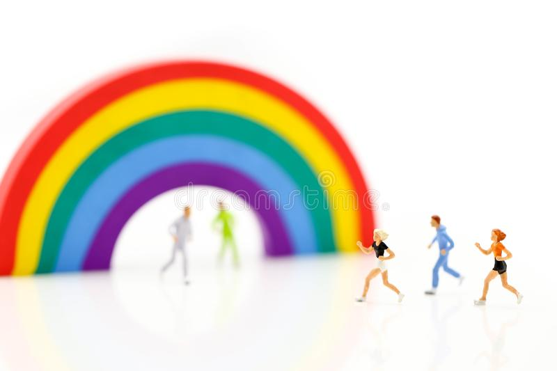 Miniaturowi ludzie: maratonów biegacze z tęczą, jogging i ru, zdjęcie royalty free
